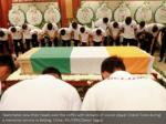 teammates bow their heads over the coffin with