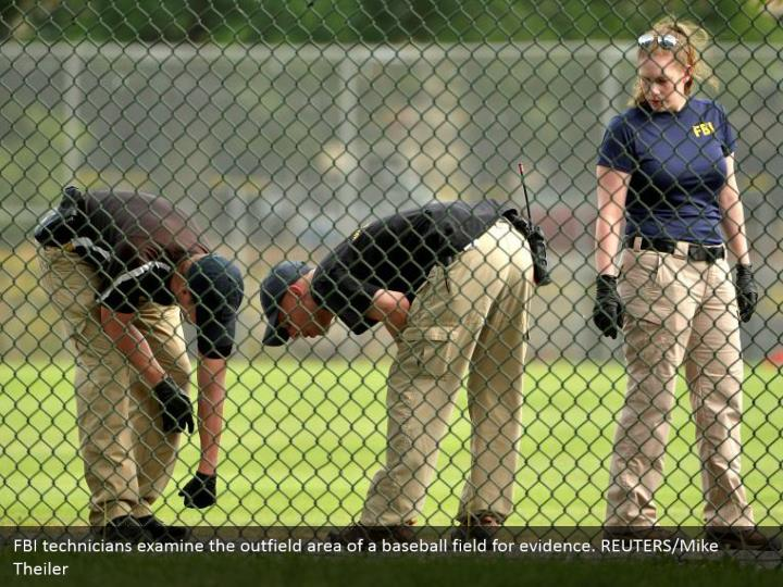 FBI technicians examine the outfield area of a baseball field for evidence. REUTERS/Mike Theiler