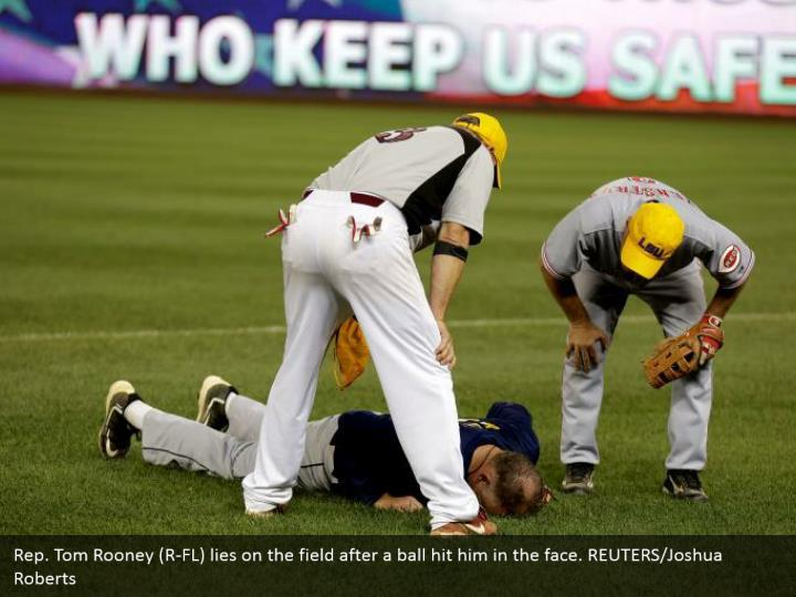 Rep. Tom Rooney (R-FL) lies on the field after a ball hit him in the face. REUTERS/Joshua Roberts