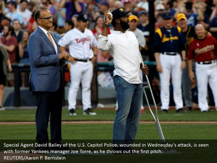 Special Agent David Bailey of the U.S. Capitol Police, wounded in Wednesday's attack, is seen with former Yankees manager Joe Torre, as he throws out the first pitch. REUTERS/Aaron P. Bernstein