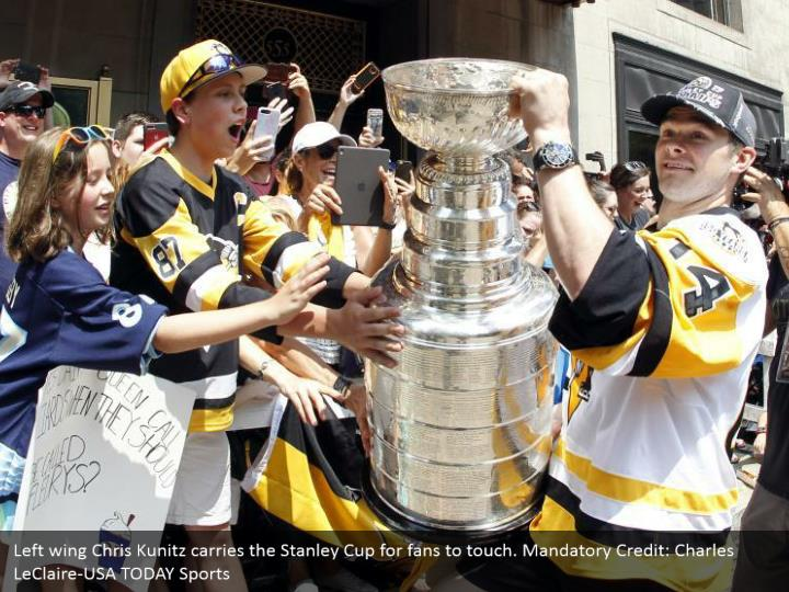 Left wing Chris Kunitz carries the Stanley Cup for fans to touch. Mandatory Credit: Charles LeClaire-USA TODAY Sports