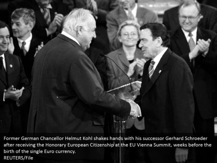 Former German Chancellor Helmut Kohl shakes hands with his successor Gerhard Schroeder after receiving the Honorary European Citizenship at the EU Vienna Summit, weeks before the birth of the single Euro currency.  REUTERS/File