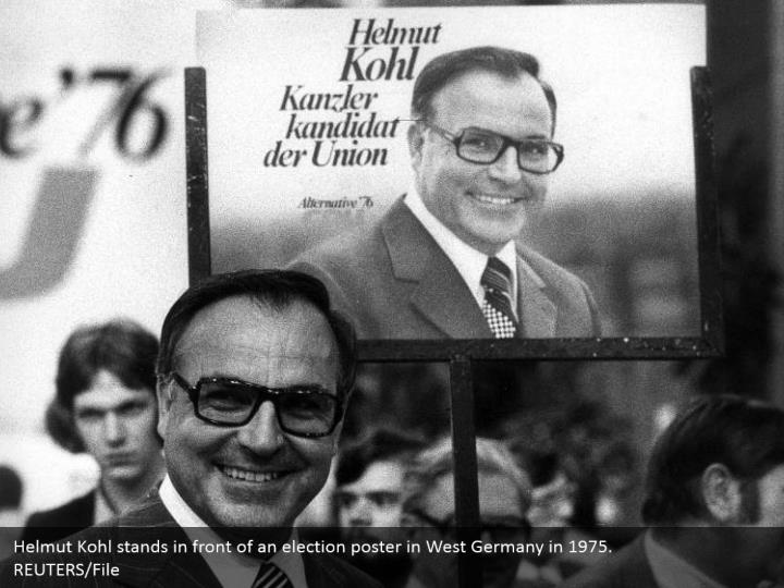 Helmut kohl stands in front of an election poster