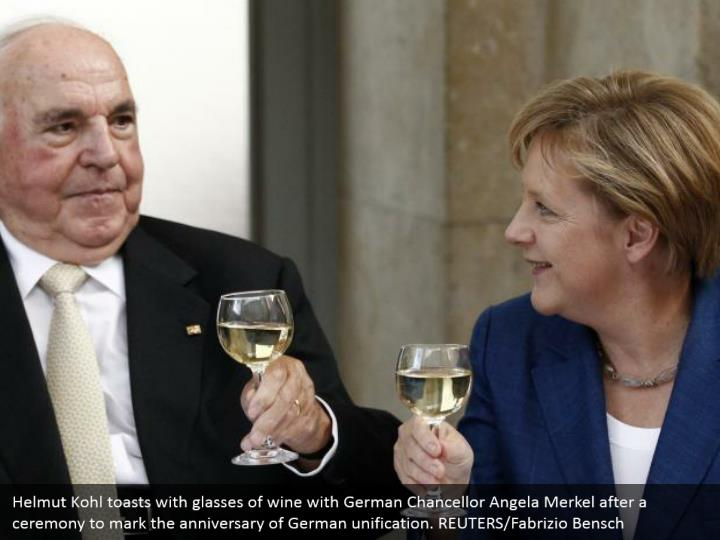 Helmut Kohl toasts with glasses of wine with German Chancellor Angela Merkel after a ceremony to mark the anniversary of German unification. REUTERS/Fabrizio Bensch