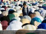 a boy watches as muslims offer eid al fitr