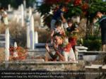 a palestinian man prays next to the grave
