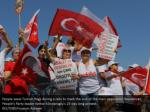 people wave turkish flags during a rally to mark