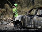 a utility worker stands next to a car burned