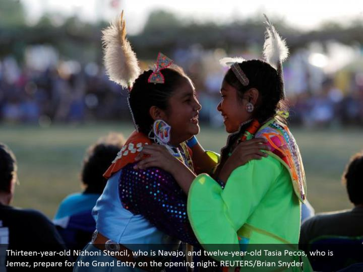 Thirteen-year-old Nizhoni Stencil, who is Navajo, and twelve-year-old Tasia Pecos, who is Jemez, prepare for the Grand Entry on the opening night. REUTERS/Brian Snyder