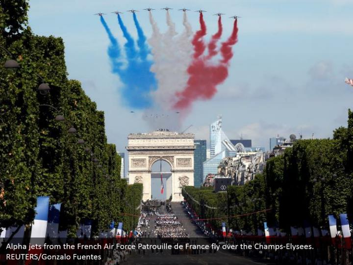 Alpha jets from the French Air Force Patrouille de France fly over the Champs-Elysees. REUTERS/Gonzalo Fuentes