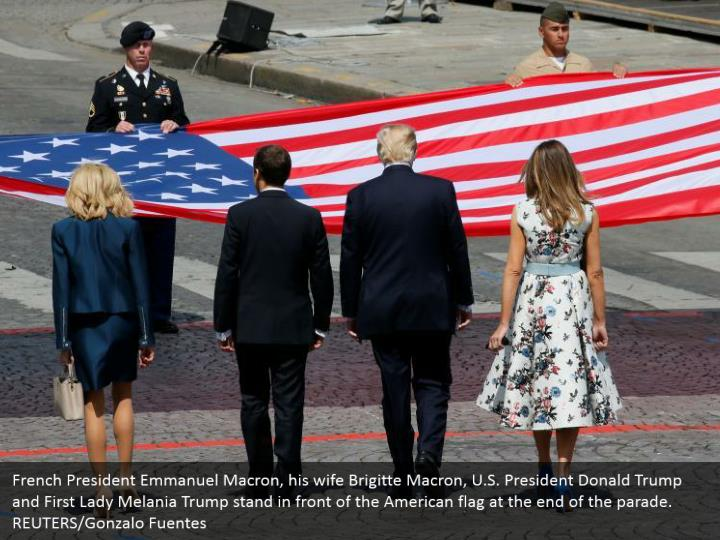 French President Emmanuel Macron, his wife Brigitte Macron, U.S. President Donald Trump and First Lady Melania Trump stand in front of the American flag at the end of the parade. REUTERS/Gonzalo Fuentes
