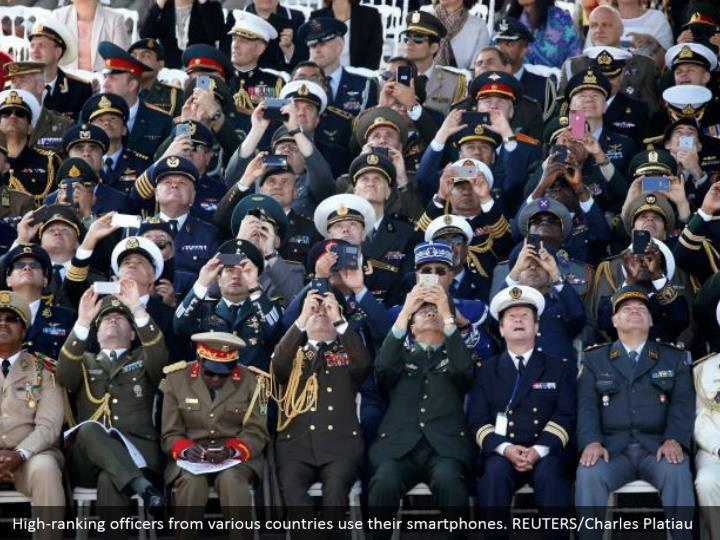 High-ranking officers from various countries use their smartphones. REUTERS/Charles Platiau