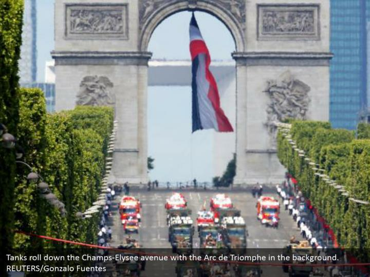 Tanks roll down the Champs-Elysee avenue with the Arc de Triomphe in the background. REUTERS/Gonzalo Fuentes