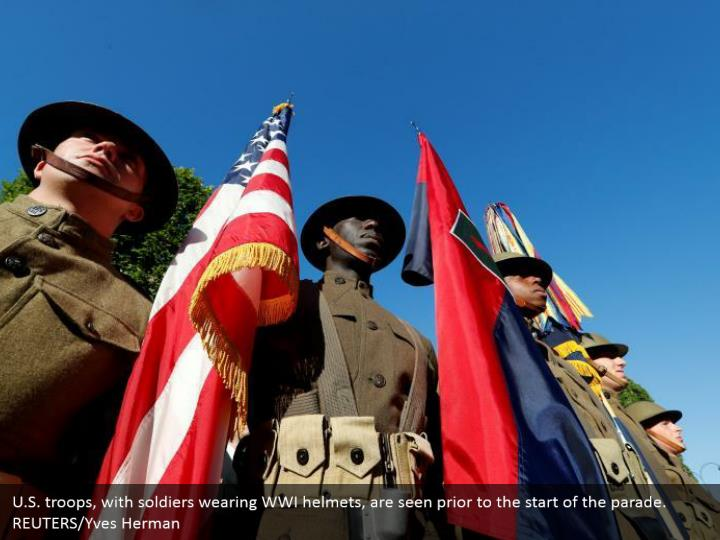 U.S. troops, with soldiers wearing WWI helmets, are seen prior to the start of the parade. REUTERS/Yves Herman