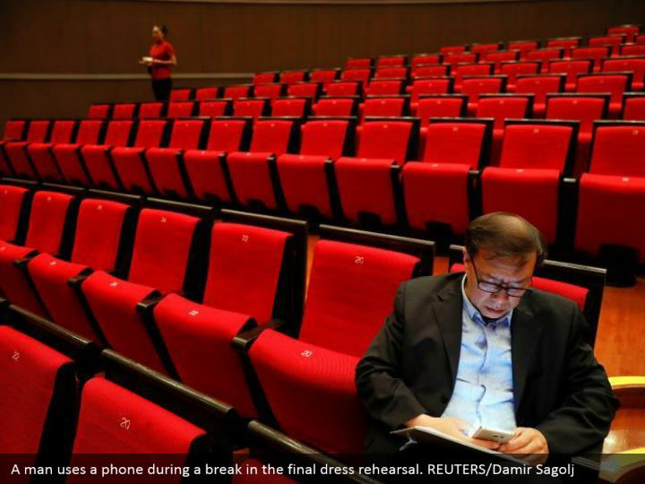 A man uses a phone during a break in the final dress rehearsal. REUTERS/Damir Sagolj