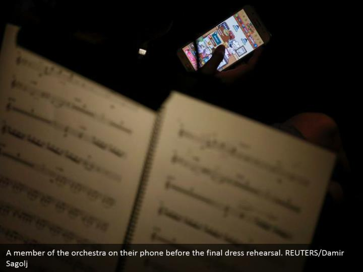 A member of the orchestra on their phone before the final dress rehearsal. REUTERS/Damir Sagolj