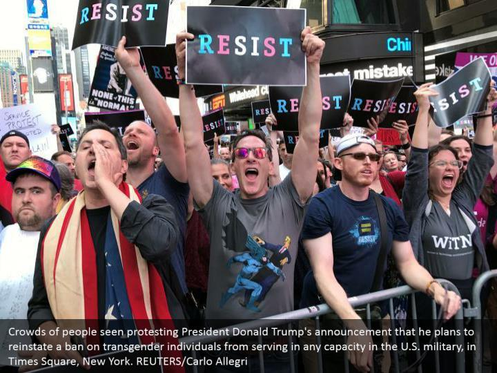 Crowds of people seen protesting President Donald Trump's announcement that he plans to reinstate a ban on transgender individuals from serving in any capacity in the U.S. military, in Times Square, New York. REUTERS/Carlo Allegri