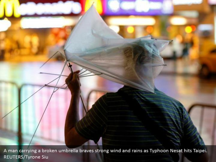 A man carrying a broken umbrella braves strong wind and rains as Typhoon Nesat hits Taipei. REUTERS/Tyrone Siu