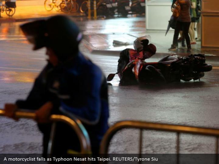 A motorcyclist falls as Typhoon Nesat hits Taipei. REUTERS/Tyrone Siu