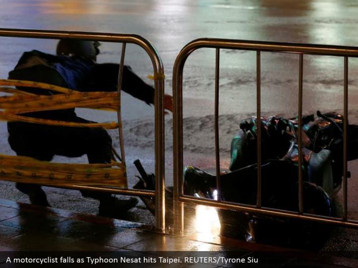 A motorcyclist falls as typhoon nesat hits taipei