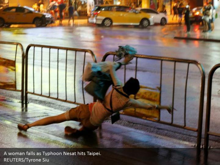A woman falls as typhoon nesat hits taipei