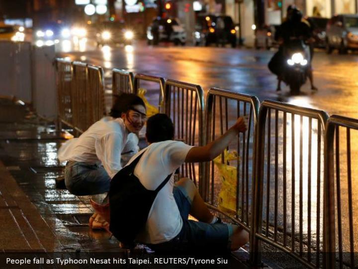 People fall as Typhoon Nesat hits Taipei. REUTERS/Tyrone Siu