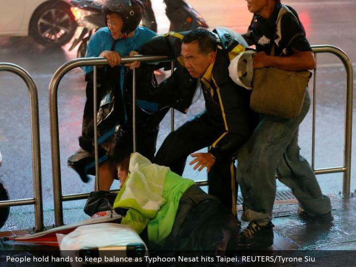 People hold hands to keep balance as Typhoon Nesat hits Taipei. REUTERS/Tyrone Siu