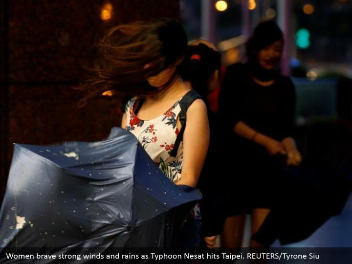 Women brave strong winds and rains as Typhoon Nesat hits Taipei. REUTERS/Tyrone Siu