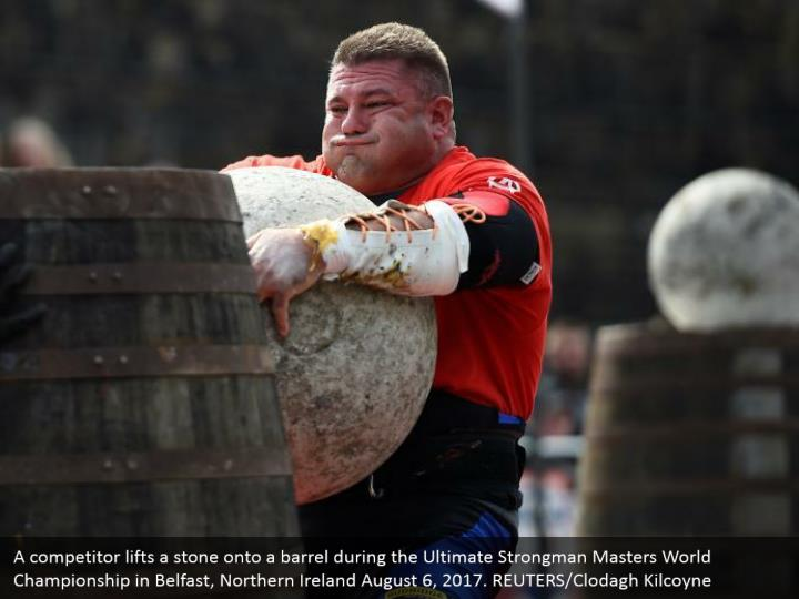A competitor lifts a stone onto a barrel during