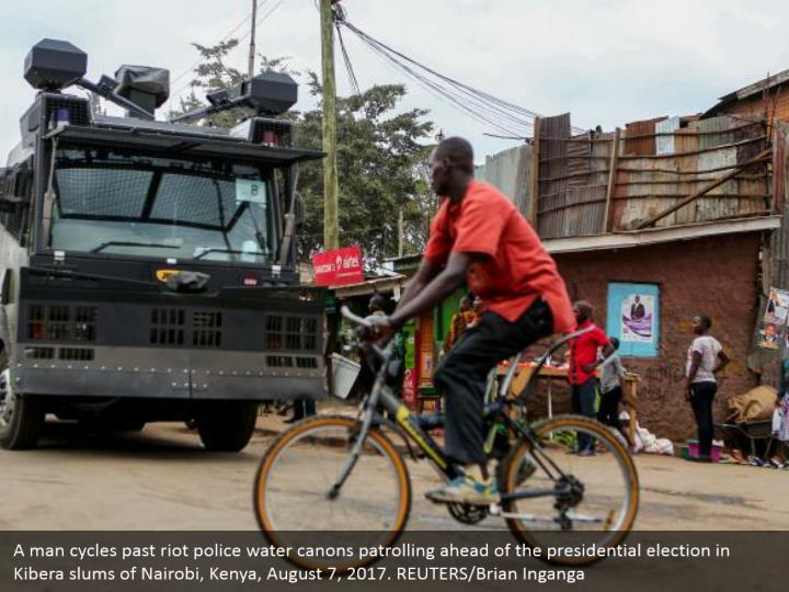 A man cycles past riot police water canons patrolling ahead of the presidential election in Kibera slums of Nairobi, Kenya, August 7, 2017. REUTERS/Brian Inganga
