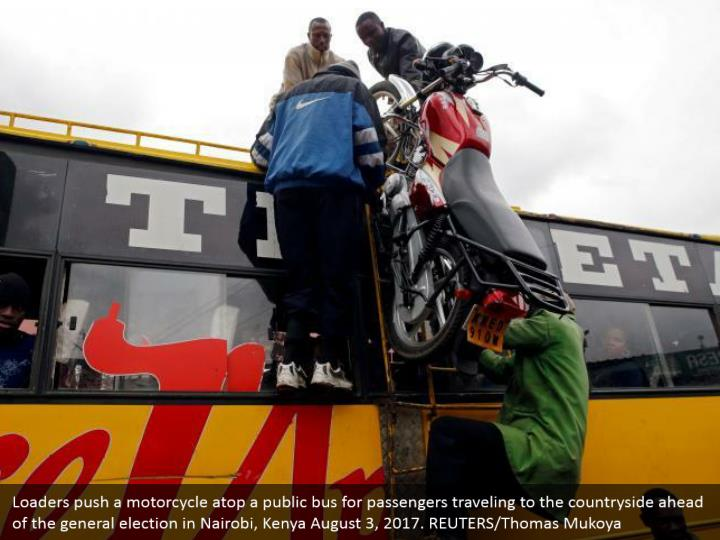 Loaders push a motorcycle atop a public bus for passengers traveling to the countryside ahead of the general election in Nairobi, Kenya August 3, 2017. REUTERS/Thomas Mukoya
