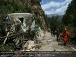 rescue workers walk past a collapsed area after