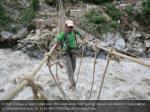 a man crosses a rope bridge over the alaknanda