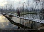 a young kashmiri walks on a wooden bridge over