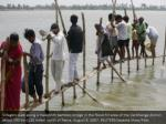 villagers walk along a makeshift bamboo bridge