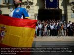 a man holds a spanish flag while authorities