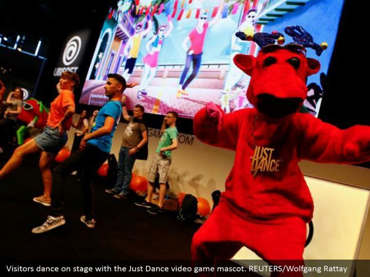 b877f00d1532 Visitors dance on stage with the Just Dance video game mascot.