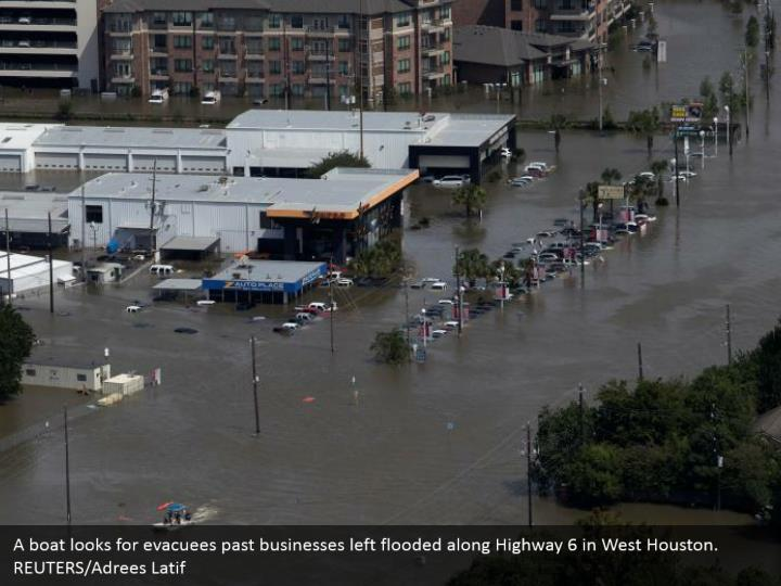 A boat looks for evacuees past businesses left flooded along Highway 6 in West Houston. REUTERS/Adrees Latif