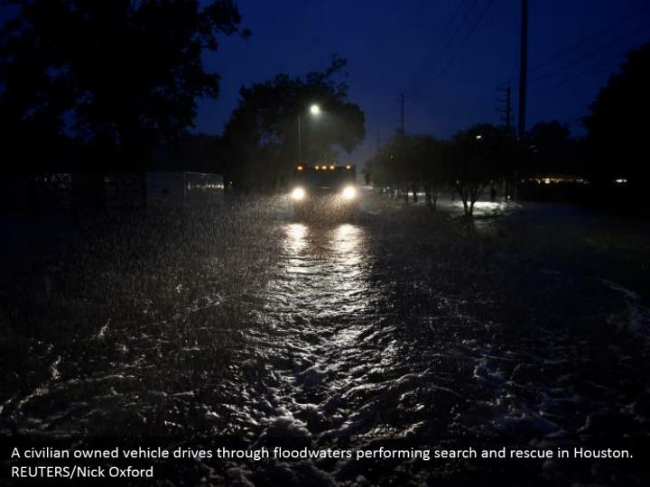 A civilian owned vehicle drives through floodwaters performing search and rescue in Houston. REUTERS/Nick Oxford