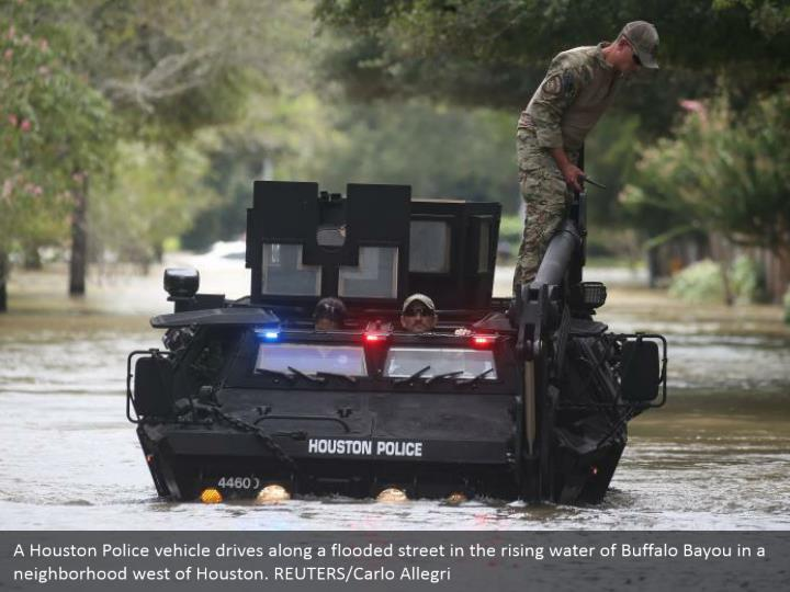 A Houston Police vehicle drives along a flooded street in the rising water of Buffalo Bayou in a neighborhood west of Houston. REUTERS/Carlo Allegri