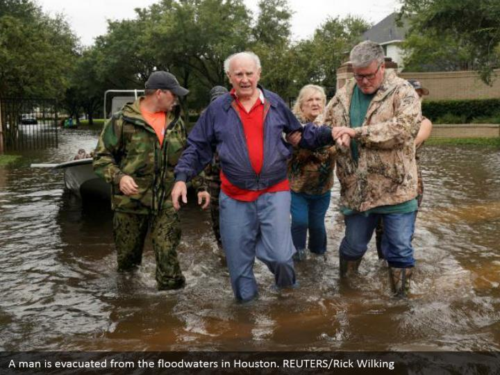 A man is evacuated from the floodwaters in Houston. REUTERS/Rick Wilking