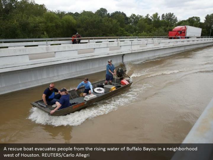 A rescue boat evacuates people from the rising water of Buffalo Bayou in a neighborhood west of Houston. REUTERS/Carlo Allegri