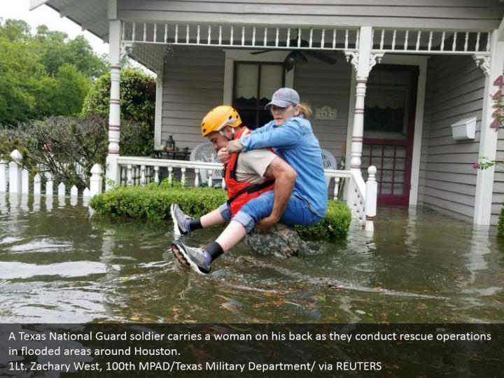 A Texas National Guard soldier carries a woman on his back as they conduct rescue operations in flooded areas around Houston.  1Lt. Zachary West, 100th MPAD/Texas Military Department/ via REUTERS