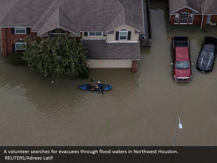 A volunteer searches for evacuees through flood waters in Northwest Houston.  REUTERS/Adrees Latif