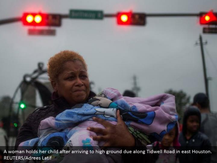A woman holds her child after arriving to high ground due along Tidwell Road in east Houston. REUTERS/Adrees Latif