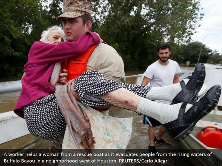A worker helps a woman from a rescue boat as it evacuates people from the rising waters of Buffalo Bayou in a neighborhood west of Houston. REUTERS/Carlo Allegri