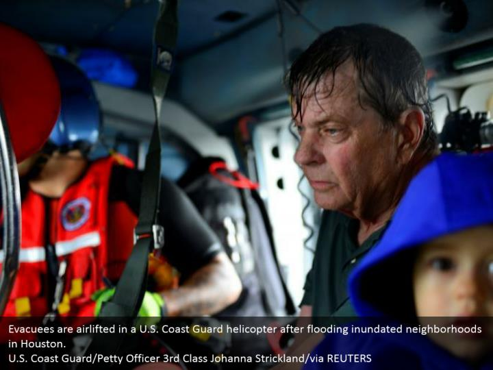 Evacuees are airlifted in a U.S. Coast Guard helicopter after flooding inundated neighborhoods in Houston.  U.S. Coast Guard/Petty Officer 3rd Class Johanna Strickland/via REUTERS