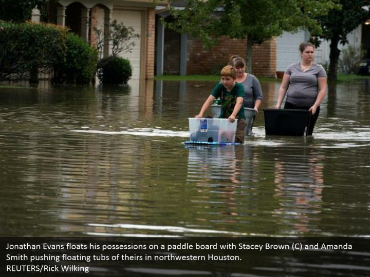 Jonathan Evans floats his possessions on a paddle board with Stacey Brown (C) and Amanda Smith pushing floating tubs of theirs in northwestern Houston.  REUTERS/Rick Wilking