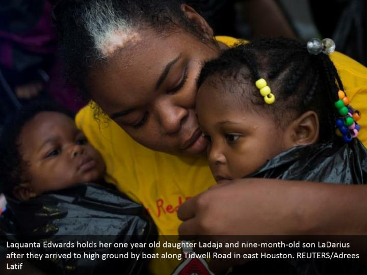 Laquanta Edwards holds her one year old daughter Ladaja and nine-month-old son LaDarius after they arrived to high ground by boat along Tidwell Road in east Houston. REUTERS/Adrees Latif