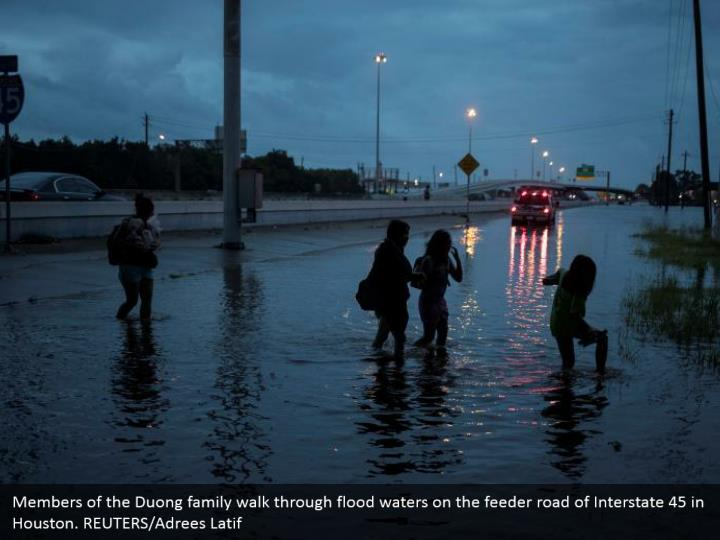 Members of the Duong family walk through flood waters on the feeder road of Interstate 45 in Houston. REUTERS/Adrees Latif